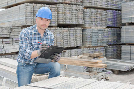 merchant: Workman stood with cast concrete slabs Stock Photo