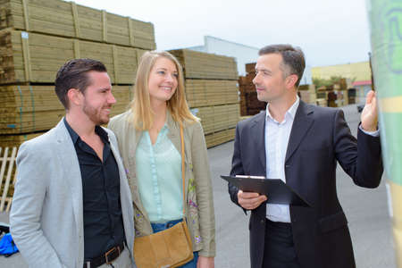 merchant: Man showing couple around a builders yard Stock Photo