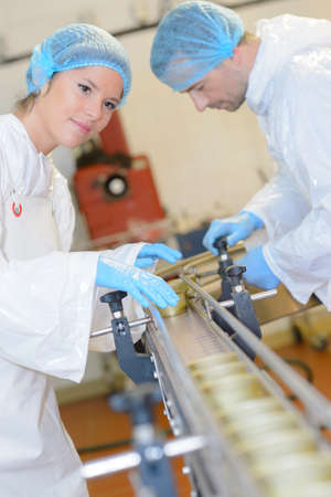 Two factory operatives working on production line