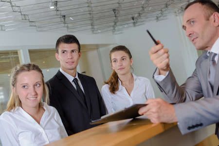 new recruits: Man at reception desk with young staff pointing left