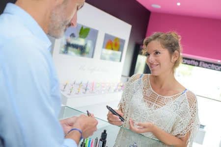 shop assistant: Shop assistant and customer at shop counter