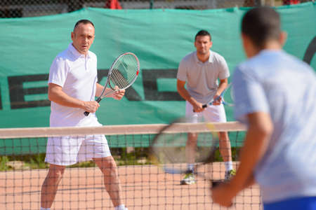serf: Men playing tennis doubles