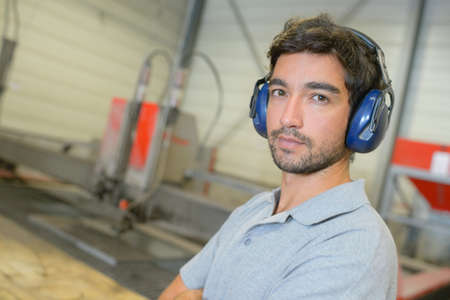 anti noise: Portrait of man in factory, wearing earmuffs Stock Photo