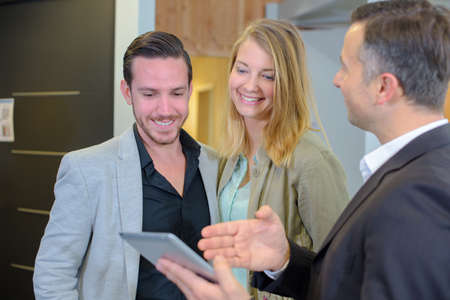 Salesman showing  screen of tablet to a couple