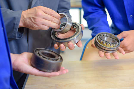 rubber gasket: Three men holding bearings