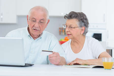transact: elderly couple purchasing something from the internet