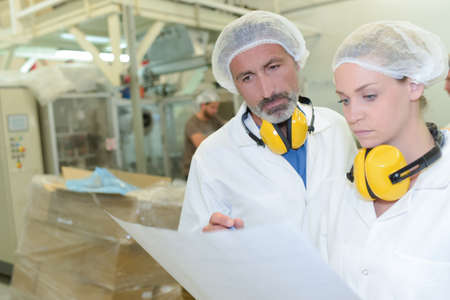 confer: Male and female factory operatives looking at paperwork