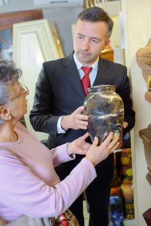 director de la funeraria con la viuda elegir urna Foto de archivo