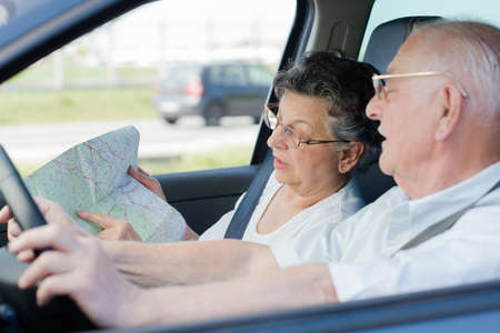 Elderly couple in car, looking at map