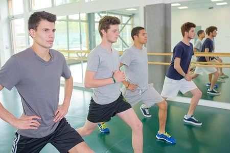 men exercising: Cuatro jóvenes que ejercitan en gimnasia