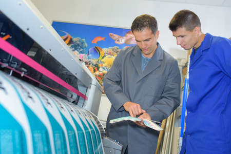 manufacturing equipment: Two men stood by industrial printer