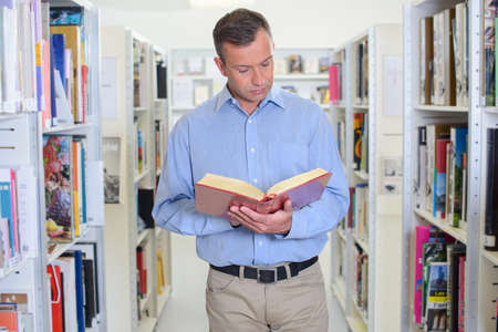 biographer: reading book in the aisle