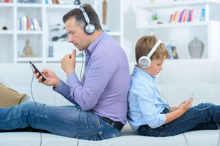 unclear: Man and child sat back to back listening to headphones Stock Photo