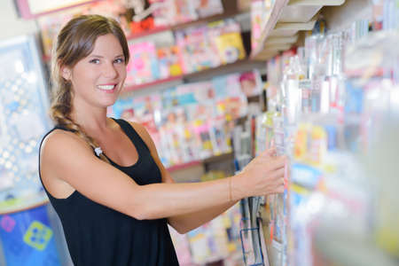 shop keeper: Lady arranging magazines on shelf in newsagents