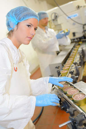 hombres trabajando: alimentos procesados ??en las latas Foto de archivo