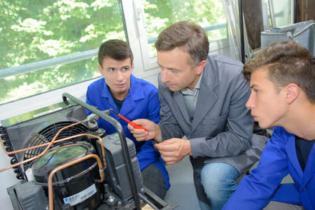 Apprentice electricians looking at electrical unit with instructor Stock Photo