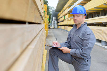 assessing: Man with clipboard assessing stack of wood Stock Photo