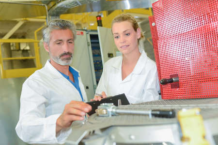 machine operator: Man and woman in factory Stock Photo