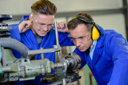 Engineer using machine apprentice with fingers in ears Фото со стока - 51230629