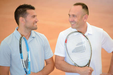 funny guys: Two men joking together, holding tennis rackets