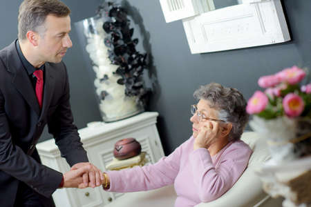 bereavement: Funeral director holding hand of elderly lady