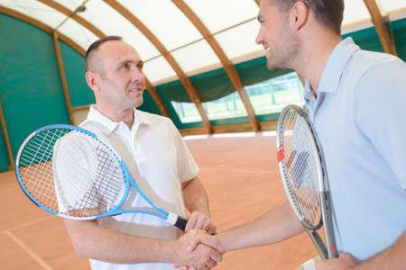 sportsmanship: Men shaking hands on tennis court