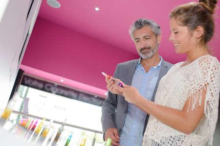 shop assistant: Shop assistant showing vaporiser to customer Stock Photo