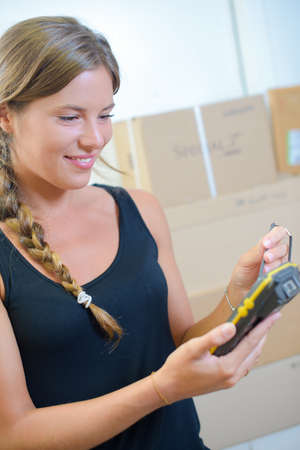 handheld device: young woman using a hand-held inventory device