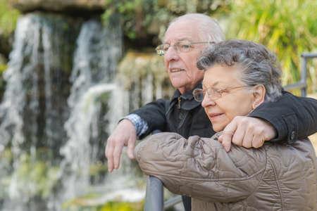 man waterfalls: Elderly couple looking at view of waterfall