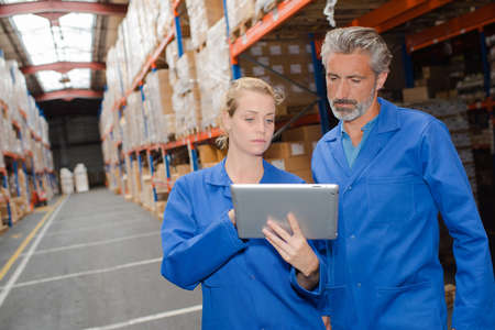computerised: Man and woman looking at tablet in warehouse Stock Photo