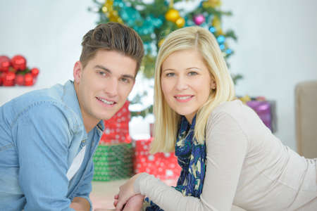 young tree: Portrait of couple in front of christmas tree