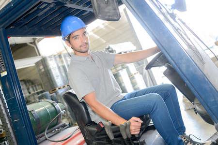 fork lift: Man driving fork lift Stock Photo