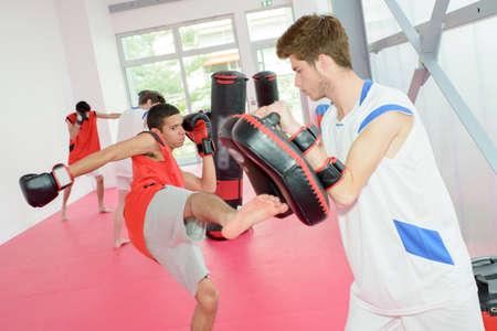 sportsmanship: young man kicking a padding