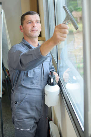 indoors: Man cleaning window indoors