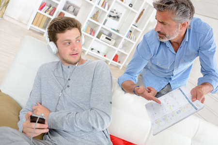 nonchalant: Man holding book and demanding explanation from teenager listening to headphones Stock Photo