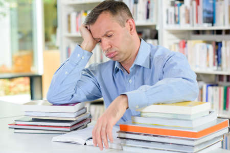 disheartened: Tired man with stack of books Stock Photo