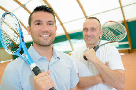 double game: Two men with tennis rackets on their shoulders
