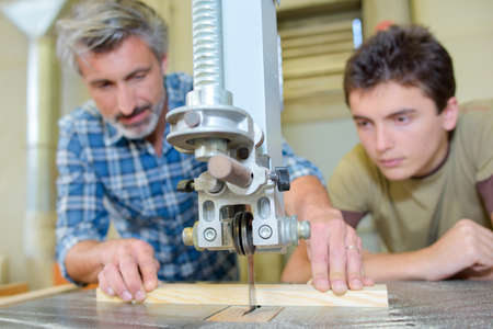 carpenter's bench: Carpenter teaching apprentice to use a bench saw