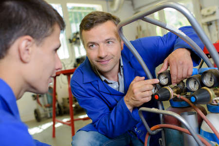 manufacturing equipment: Man with trainee pointing to gauge Stock Photo