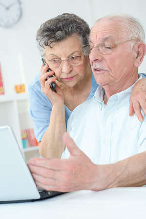 helpline: Elderly couple using laptop, wife on telephone Stock Photo