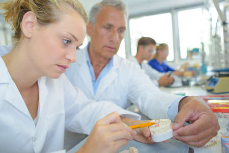 supervisor: Supervisor guiding lady in manufacture of dentures Stock Photo
