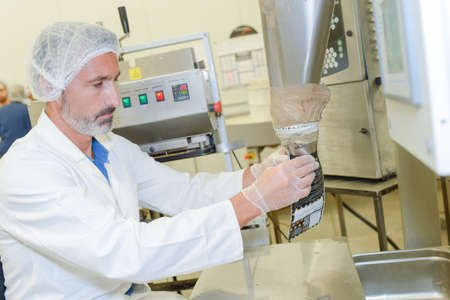 food industry: man putting processed food in a bag