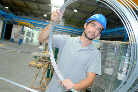 Industrial workers: young man holding a wire roll