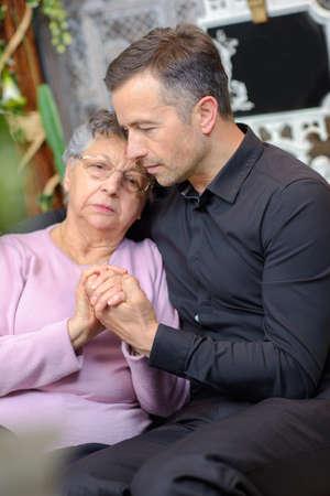 bereavement: Man comforting elderly woman Stock Photo