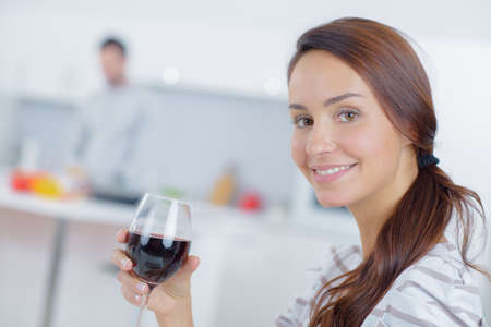 role reversal: Lady holding glass of wine, partner in background Stock Photo