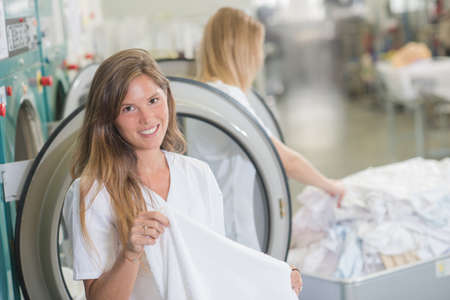 launderette: Women working in professional launderette Stock Photo