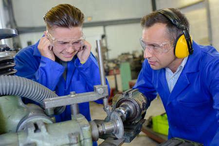 ruido: El hombre joven proteger los oídos de maquinaria ruidosa