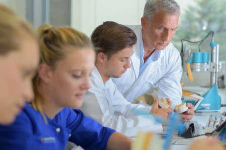 supervisor: Supervisor checking dentures in lab