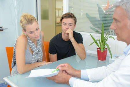 information point: Doctor showing paperwork to couple in office Stock Photo