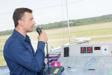Man in control tower speaking into microphone